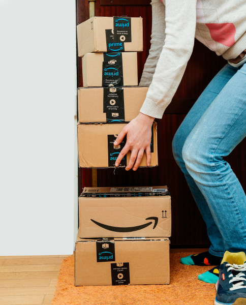 Woman lifting heavy Amazon cardboard boxes